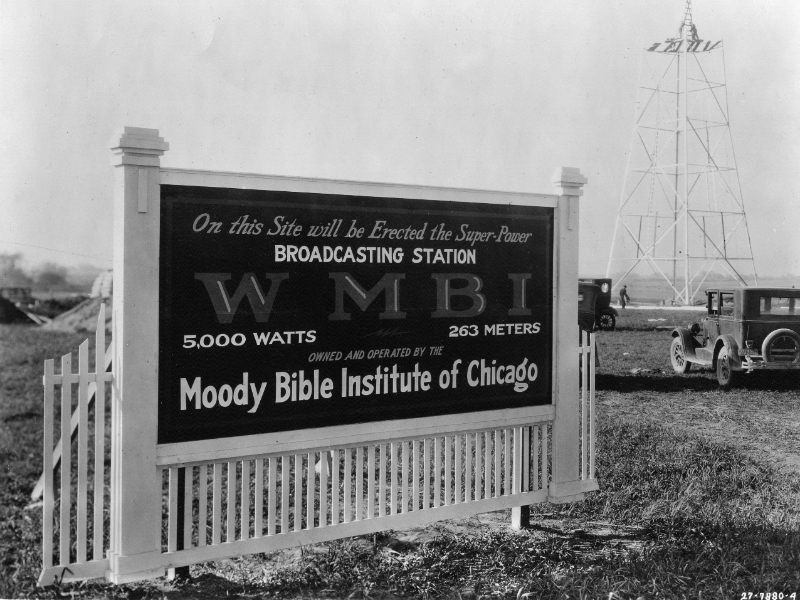 The original sign for the WMBI transmitter site stands in the forground. It says, On this site will be erected the super-power broadcasting station WMBI, owned and operated by the Moody Bible Institute of Chicago. In the background, men assemble the new tower for the transmitter.